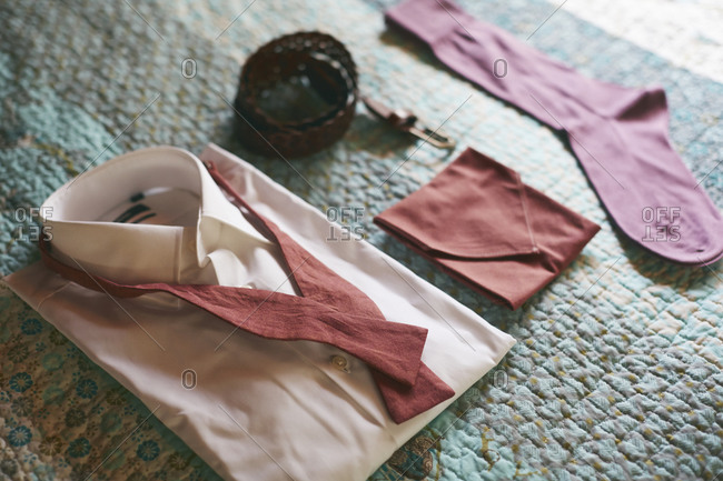 A men's accessories arranged on a quilt