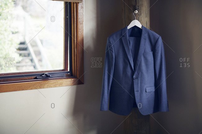 A blue suit hanging in a room by a window