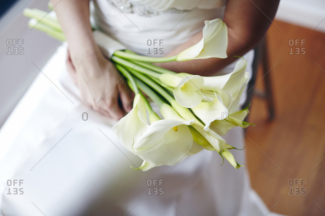 Close up of a bride and a bouquet of lilies