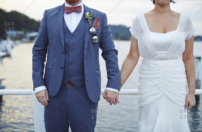 A bride and groom hold hands on a jetty at dusk