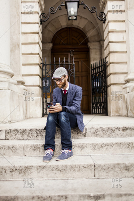 Hip man on steps with phone