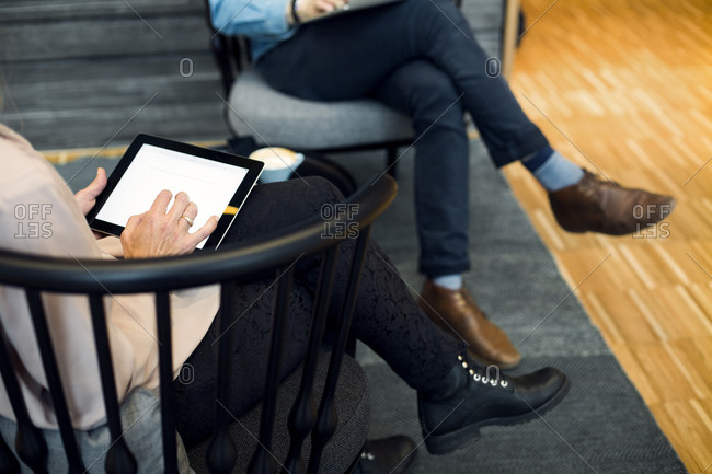 Woman on tablet near man