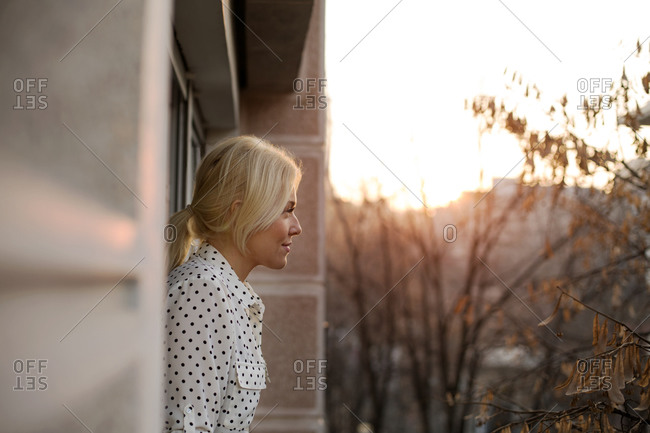 Woman in polka dot blouse standing on a balcony