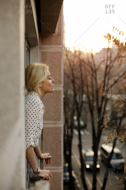 Woman in polka dot blouse standing on a balcony with eyes closed