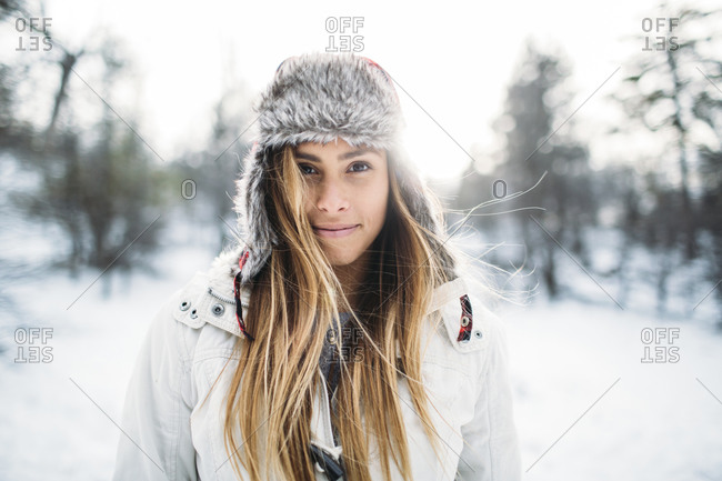 Portrait of a young woman with a furry hat in the winter