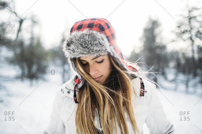 Portrait of a young woman with a furry hat looking down