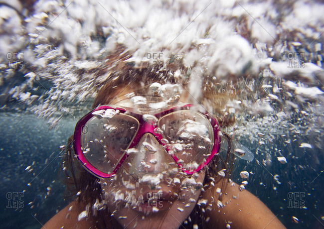 Young woman underwater blowing bubbles