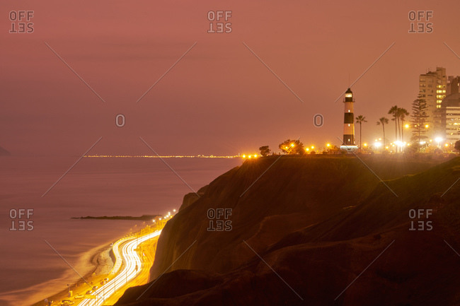 Lighthouse on a rocky cliff above a highway at twilight