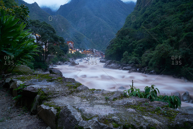 River flowing over rocks near a city at dusk