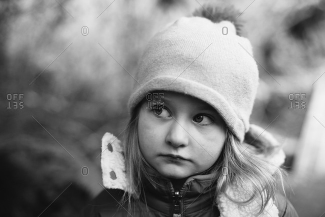 Young girl in winter hat and jacket looking sideways