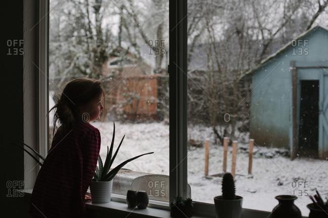 Girl leans on windowsill to watch snow falling in her backyard