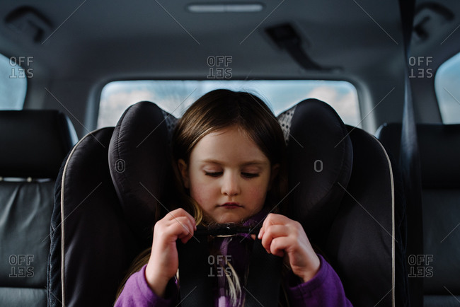 Child buckling her car seat harness