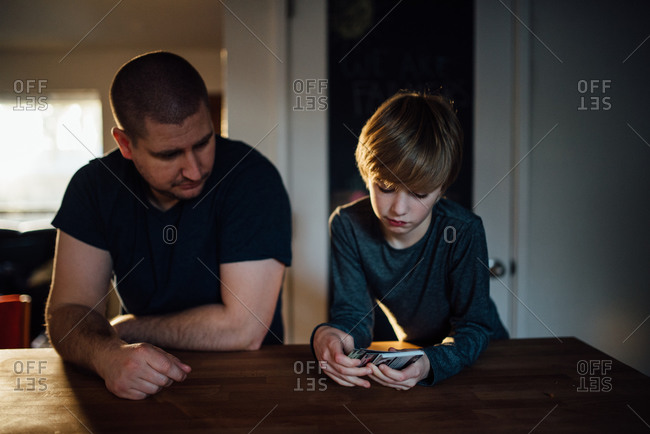 Boy showing collectible trading cards to his father