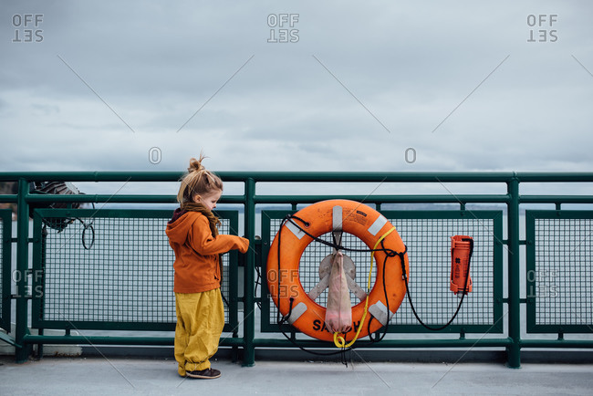 Young girl standing next to life ring on ferry boat