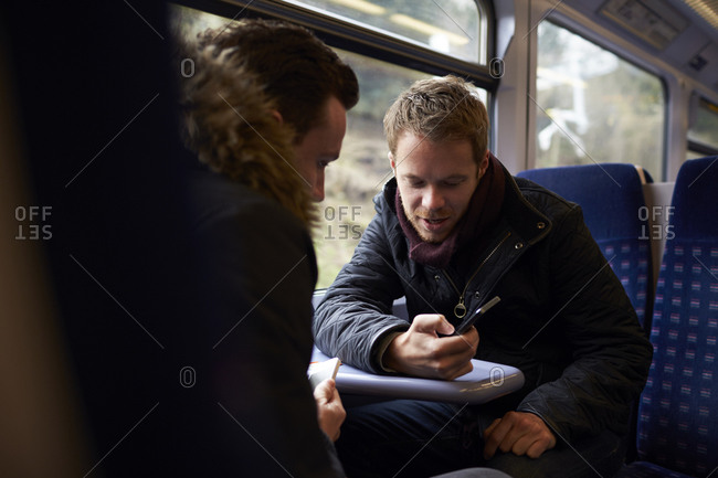 Two men sitting in train carriage looking at text message