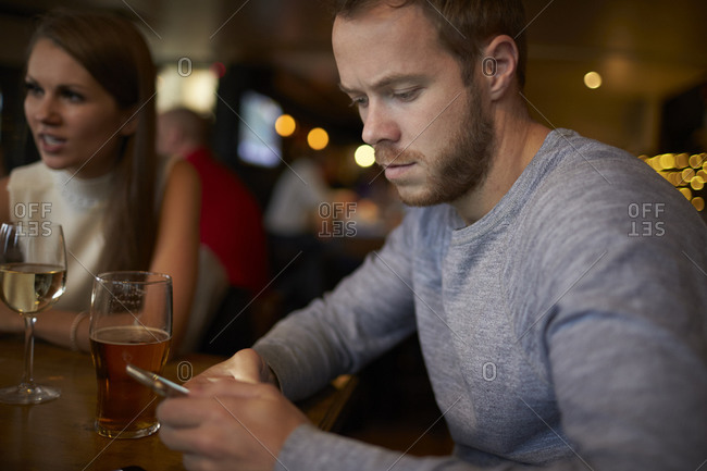 Young man sitting in bar sending text message