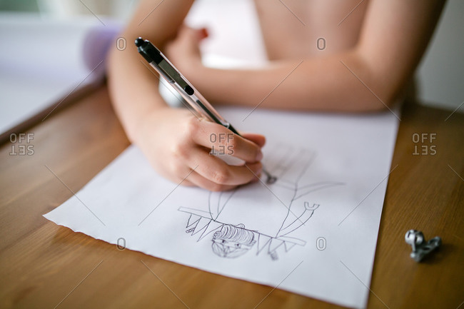 Little girl drawing a monster on a piece of paper