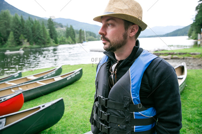 Man in a fedora and life vest standing near canoes
