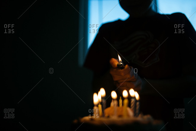Silhouette of a person lighting candles on a birthday cake