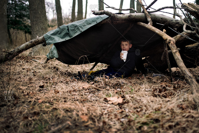 Boy sitting in a fort made from branches and a tarp