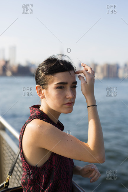 Portrait of young woman looking at the East River in Williamsburg, NY