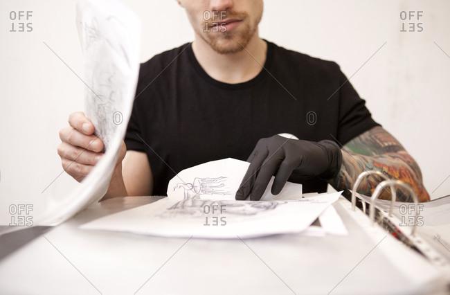 Tattoo artist with drafts in his tattoo studio