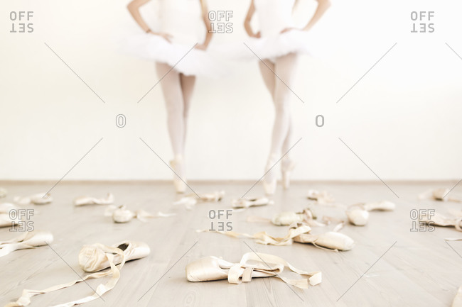 Ballet shoes scattered on the floor with two dancers in the background