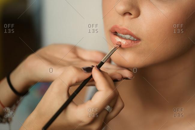 Woman having lipstick brushed on