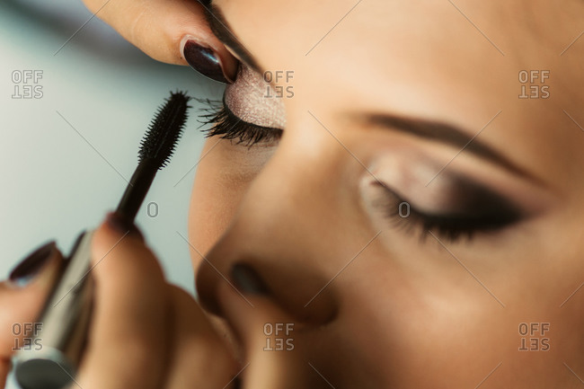 Hand putting eye shadow on woman