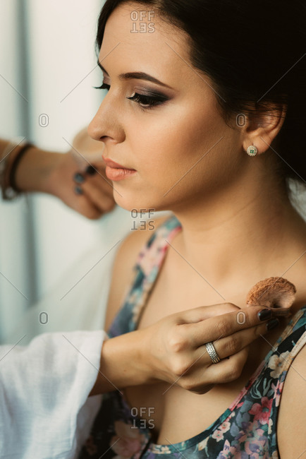 Hand putting makeup on woman