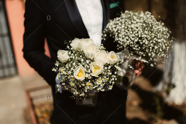 Groom holding bridal bouquets