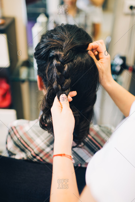 Stylist braiding woman's hair