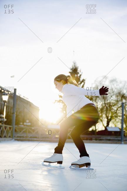 Woman figure skating at dusk