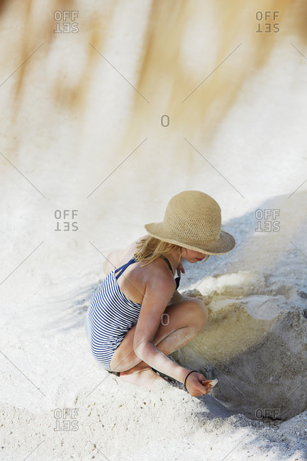 Girl digging a hole in the sand on beach