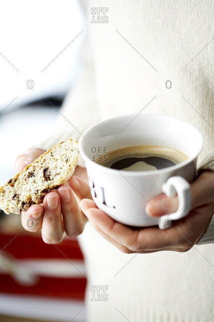 Woman holding coffee cup and biscotti