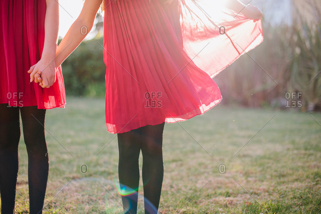 Sisters in pink dresses holding hands in a field