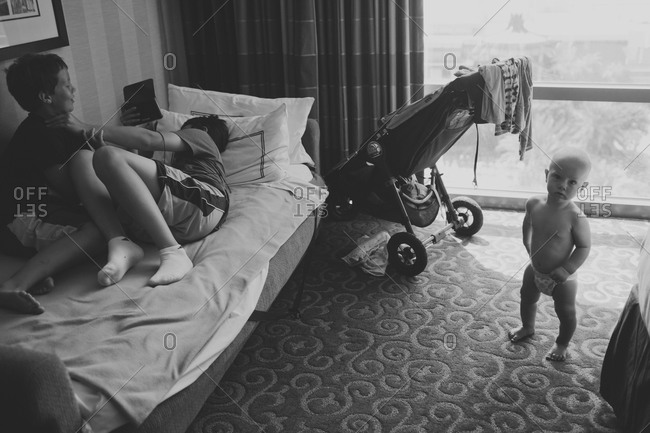 Children wrestling on a pull out couch with baby nearby