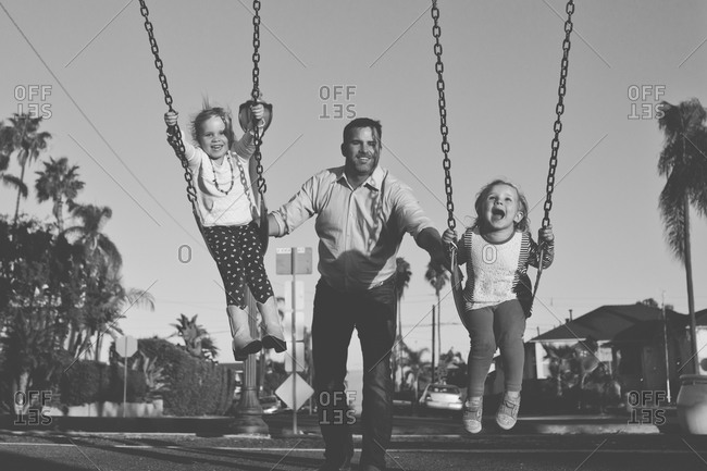 Father pushing daughter on swings in the park in black and white