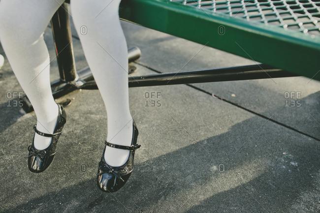 Little girl's feet dangling from a bench