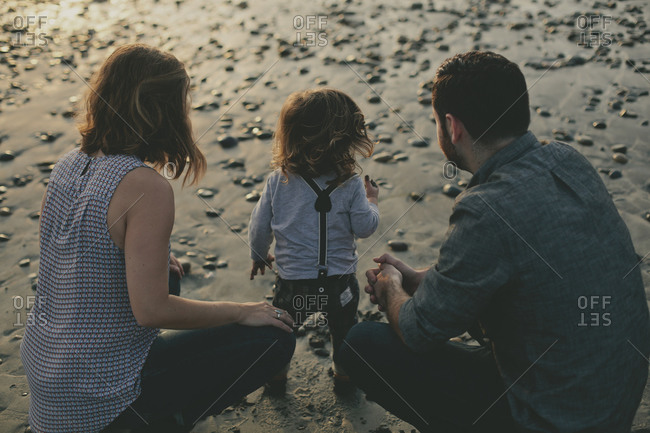 Parents and toddler standing on the beach