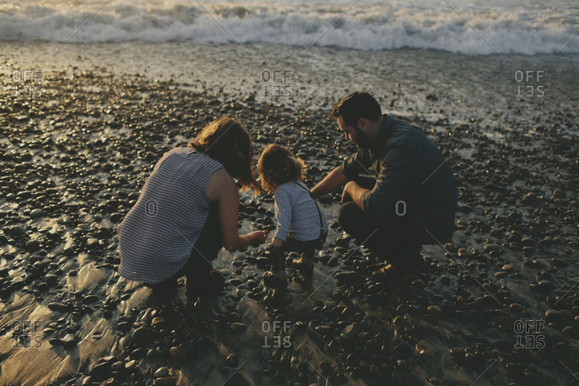 Parents and toddler squatting on the beach looking at rocks