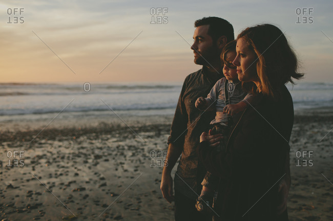 Family watching the sunset on the beach