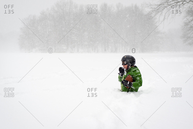 Boy with football in deep snow