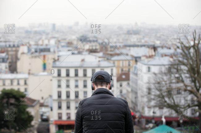 A man listening to music on headphones with a view of Paris in front of him