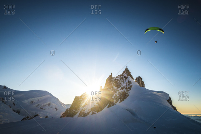 Paraglider soaring over a mountain ridge at sunset in the French Alps
