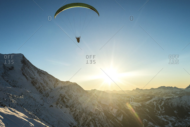 Paraglider and the sun over mountains in the French Alps