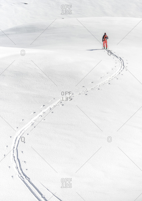 Skier and tracks on a snowy hill