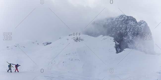 Skiers walking across a snow-covered mountain carrying their gear
