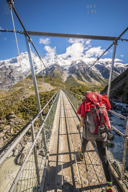 Hiker crossing a pedestrian bridge over a river near Aoraki Mount Cook, New Zealand