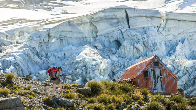 Backpacker walking toward a mountain hiker's hut at Aoraki Mount Cook, New Zealand